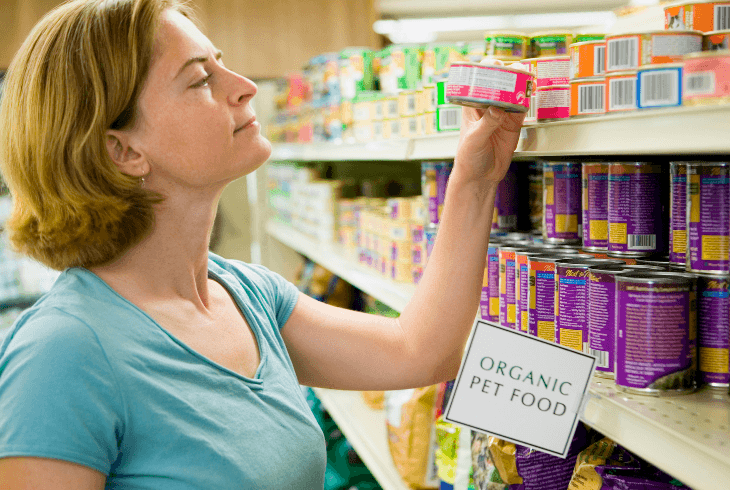 Woman reading the ingredients on a organic pet food can