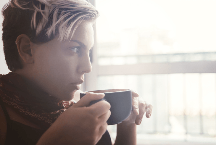 Young woman drinking coffee thinking about her dog in surgery