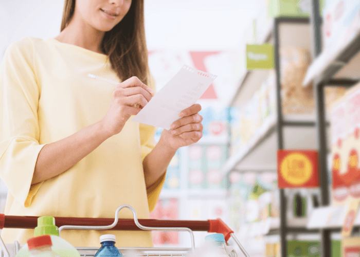 Young woman shopping for spring cleaning supplies with a list
