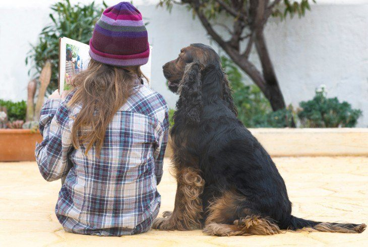 Young special needs girl reading a book with her dog