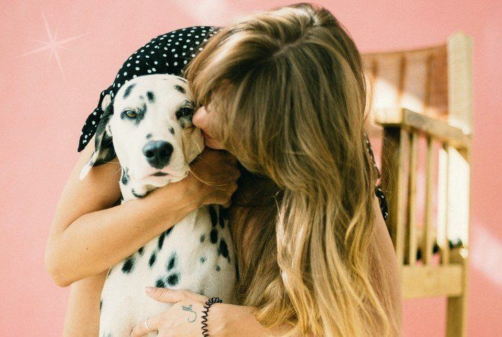 Pet owner hugging her pup after giving him cbd for dogs