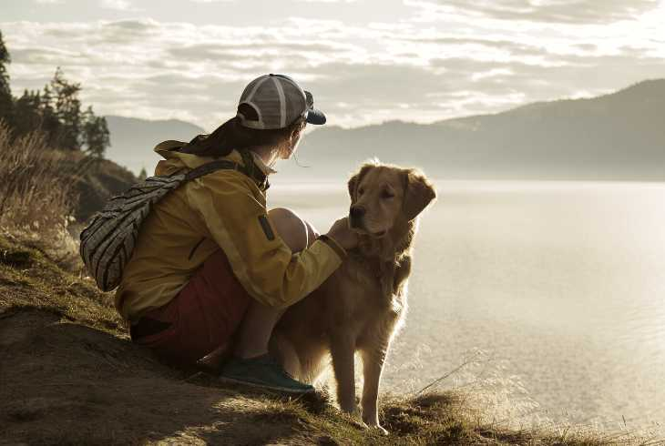 Girl and dog hiking by a lake