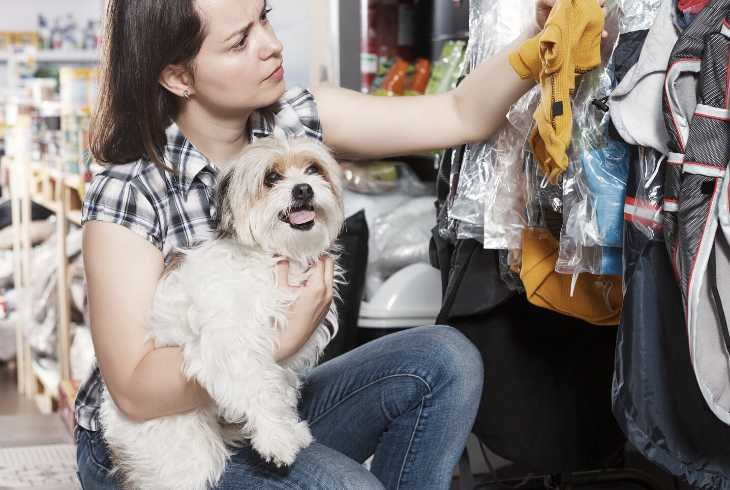 Woman and dog shopping for dog clothing