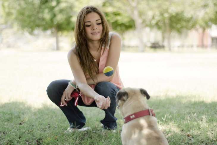 Girl introducing her dog to the ball for playing fetch